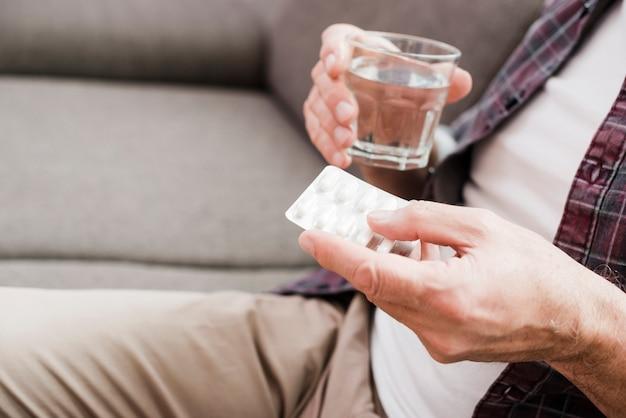 Hombre mayor tomándose sus medicinas