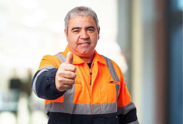 Hombre mayor con traje reflectante con el pulgar arriba