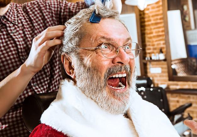 El hombre mayor en traje de santa claus afeitando a su maestro personal en la peluquería antes de navidad