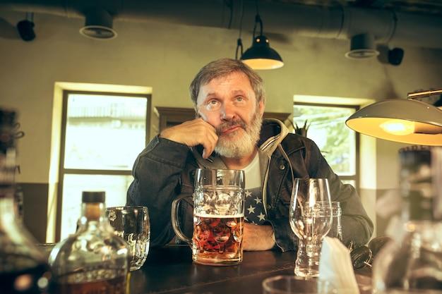 Hombre mayor triste bebiendo alcohol en el pub y viendo un programa deportivo en la televisión