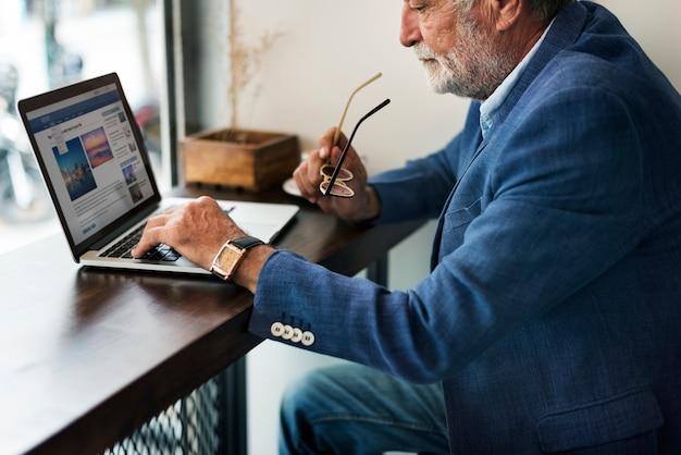 El hombre mayor está utilizando la computadora portátil