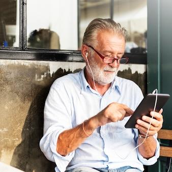 Hombre mayor está utilizando tableta digital