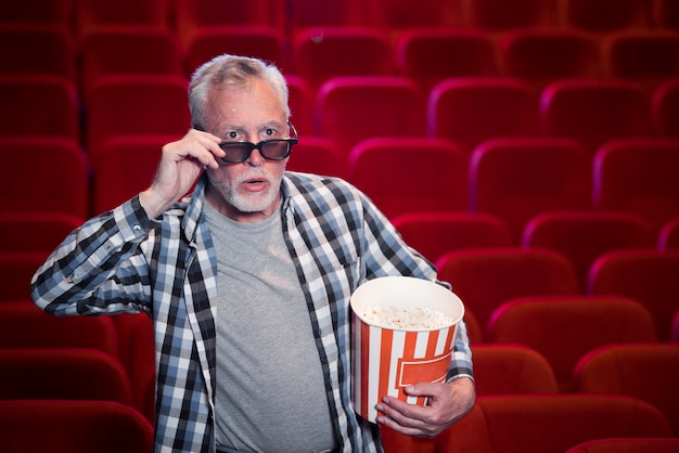 Hombre mayor viendo película en cine