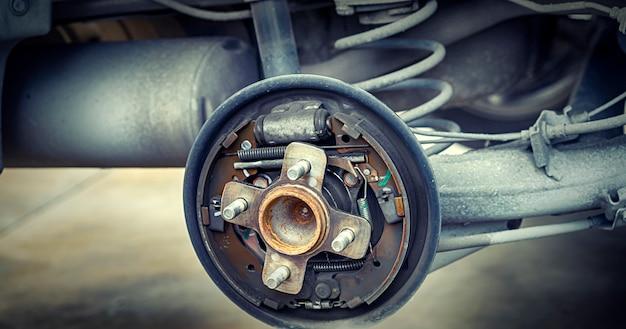 Hombre con mecánico de automóviles bloquear la rueda del viento. para revisar las llantas y los frenos del automóvil. mecánico automático preparación para el trabajo.