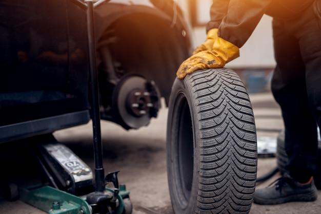 Hombre mecánico de automóviles con destornillador eléctrico cambiando neumáticos afuera. servicio de auto. las manos reemplazan los neumáticos de las ruedas. concepto de instalación de neumáticos.