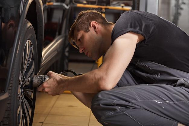 Hombre mecánico de automóviles profesional concentrado repara una rueda que se ha roto