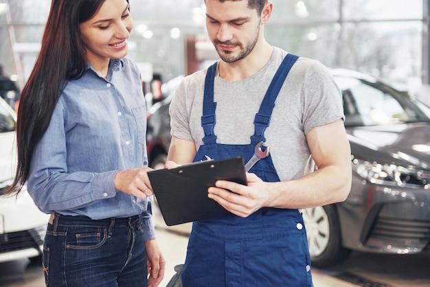 Un hombre mecánico y una clienta discutiendo reparaciones hechas a su vehículo