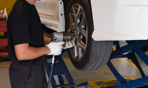 Hombre mecánico con herramienta de llave de impacto cambiando neumáticos de automóvil en taller de autoservicio