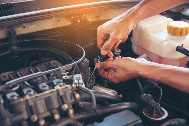 Hombre mecánico manos coche de fijación en el centro de automoción móvil.