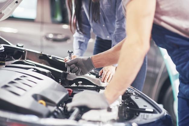 Un hombre mecánico y una mujer cliente miran el capó del automóvil y discuten las reparaciones