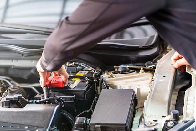 El hombre mecánico revisa la cubierta del poste de la batería, la inspección y la mentalidad