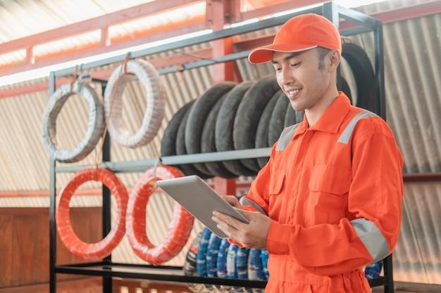 Un hombre mecánico en wearpack usando una tableta digital mientras está en el taller con una rejilla para neumáticos detrás