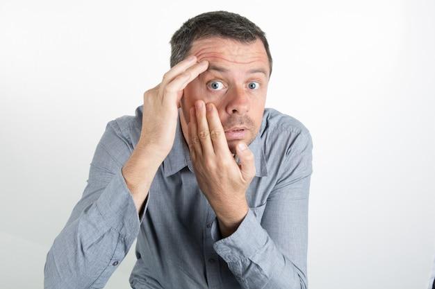 Hombre de mediana edad aplicando loción facial aislada