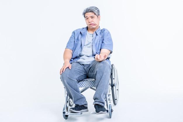 Hombre de mediana edad asiático sentado en una silla de ruedas sus manos están dobladas debido a un