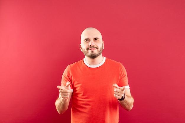Un hombre de mediana edad con barba y camiseta roja se encuentra regocijado por la victoria. aislado.