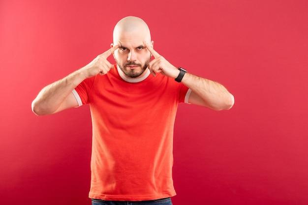 Un hombre de mediana edad con barba y una camiseta roja muestra su mano con un arma en la sien. aislado.