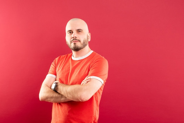 Un hombre de mediana edad con barba y camiseta roja señala alegremente a la derecha. aislado.