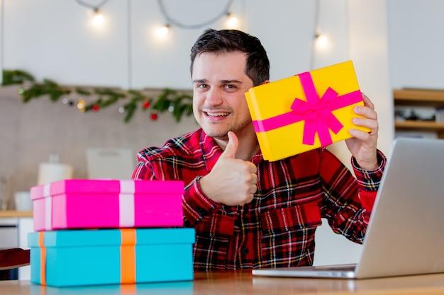 Hombre de mediana edad blanco en camiseta roja sosteniendo una caja de regalo y buscando ventas en internet a través de una computadora portátil en navidad.