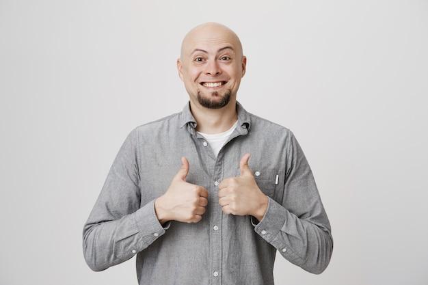 Hombre de mediana edad calvo satisfecho, sonriendo y mostrando el pulgar hacia arriba