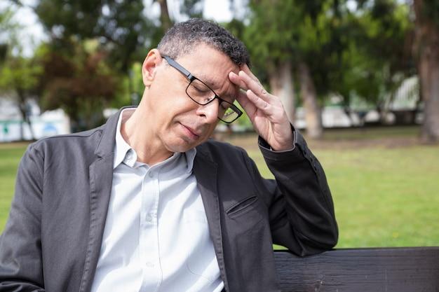 Hombre de mediana edad cansado que toca la cabeza y que se sienta en banco en parque