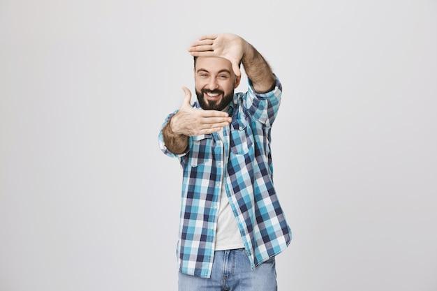 Hombre de mediana edad creativo captura el momento, muestra el gesto de los marcos de la mano