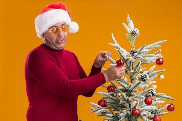 Hombre de mediana edad divertido con gorro de papá noel de navidad en cuello alto rojo oscuro y gafas amarillas sacando la lengua decorando el árbol de navidad parado sobre la pared naranja