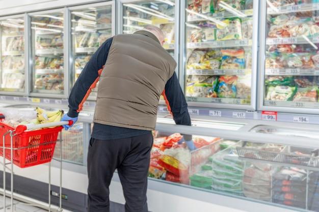 Un hombre de mediana edad elige alimentos congelados en el refrigerador de un supermercado. vista trasera. alimentación saludable