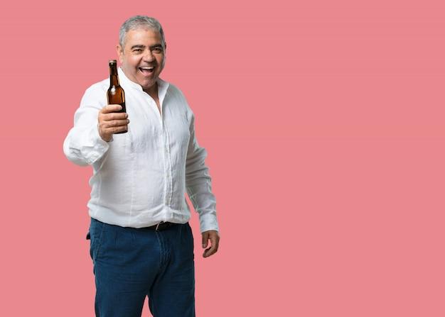 Hombre de mediana edad, feliz y divertido, sosteniendo una botella de cerveza, se siente bien después de un intenso día de trabajo.