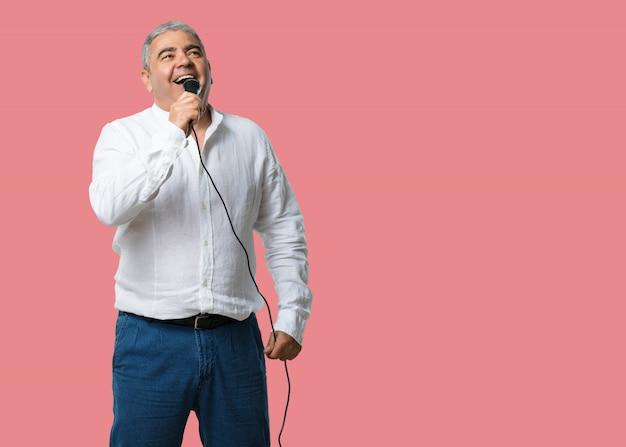 Hombre de mediana edad feliz y motivado, cantando una canción con un micrófono.