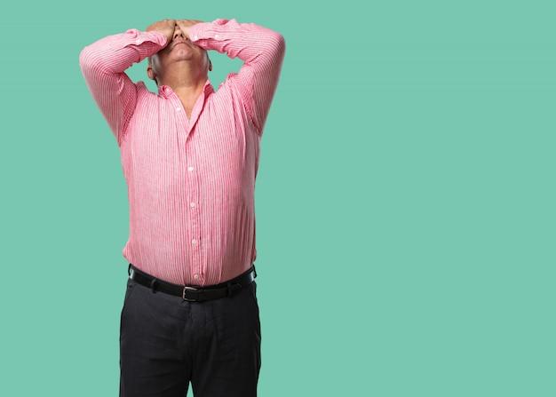 Hombre de mediana edad frustrado y desesperado, enojado y triste con las manos en la cabeza