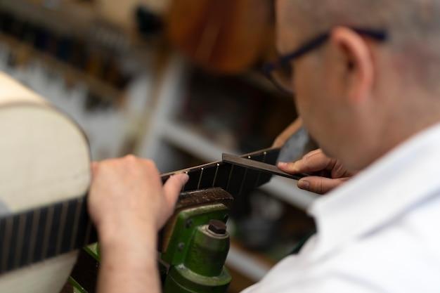 Hombre de mediana edad haciendo instrumentos en su taller solo