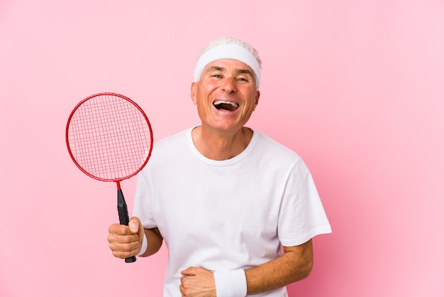 Hombre de mediana edad jugando al bádminton aislado riendo y divirtiéndose.