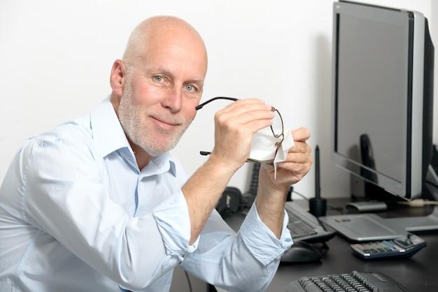 Hombre de mediana edad limpia sus gafas en su oficina