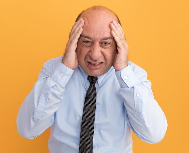Hombre de mediana edad molesto vestido con camiseta blanca con corbata poniendo las manos en las mejillas aisladas en la pared naranja