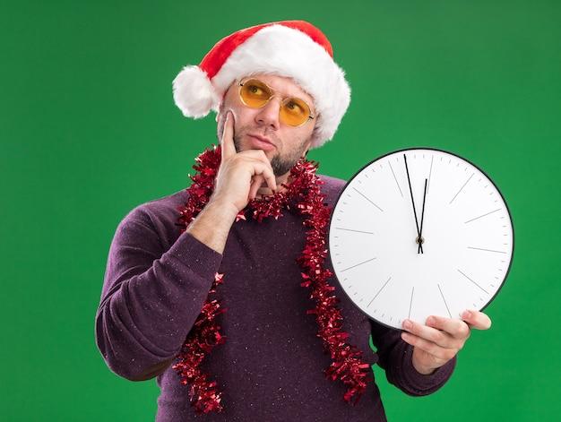 Hombre de mediana edad pensativo con gorro de papá noel y guirnalda de oropel alrededor del cuello con gafas sosteniendo el reloj manteniendo la mano en la barbilla mirando hacia arriba aislado en la pared verde