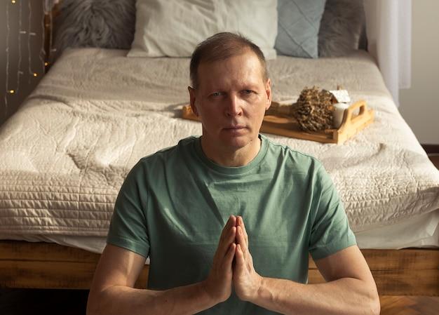 Hombre de mediana edad practicando yoga y meditación en casa ecológica