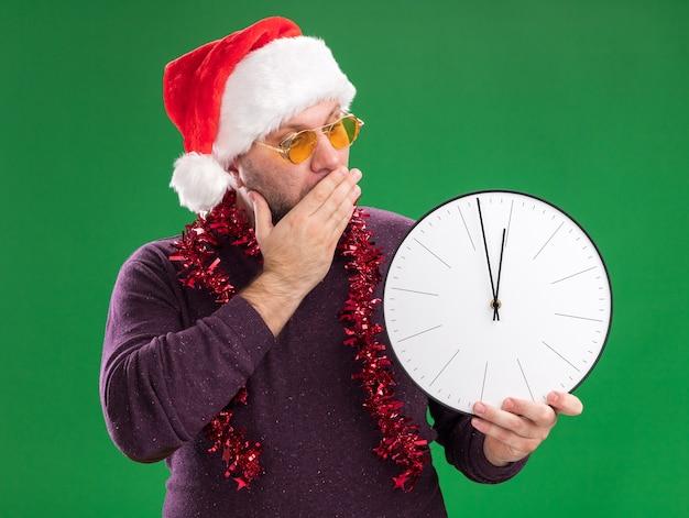 Hombre de mediana edad preocupado con gorro de papá noel y guirnalda de oropel alrededor del cuello con gafas manteniendo la mano en la boca sosteniendo y mirando el reloj aislado en la pared verde