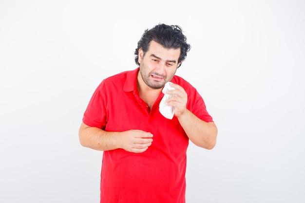 Hombre de mediana edad secándose los ojos con una servilleta mientras llora en camiseta roja y mirando ofendido, vista frontal.