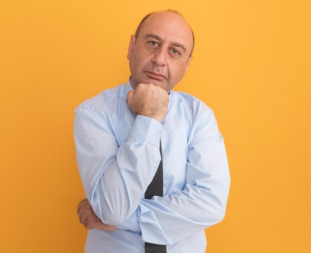 Hombre de mediana edad seguro con camiseta blanca con corbata poniendo el puño debajo de la barbilla aislado en la pared naranja