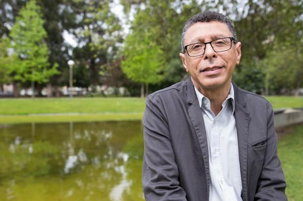 Hombre de mediana edad sonriente que presenta en la cámara en parque de la ciudad