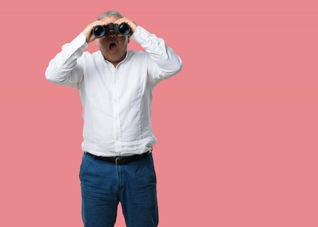 Hombre de mediana edad sorprendido y sorprendido, mirando con binoculares en la distancia algo en