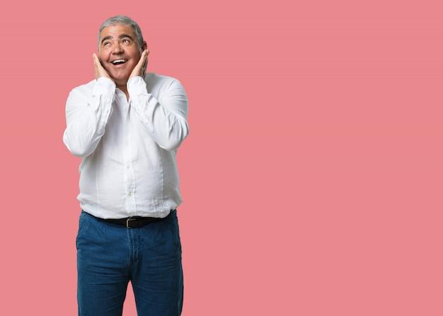 Hombre de mediana edad sorprendido y sorprendido, mirando con los ojos bien abiertos, emocionado por una oferta o por un nuevo trabajo, gana el concepto