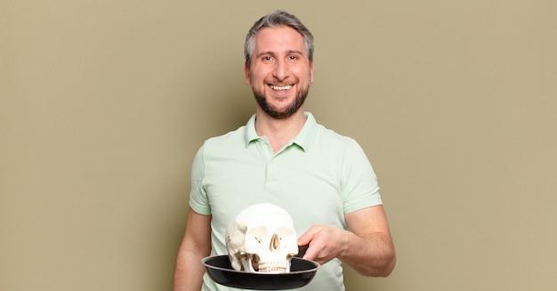Hombre de mediana edad sosteniendo un cráneo humano
