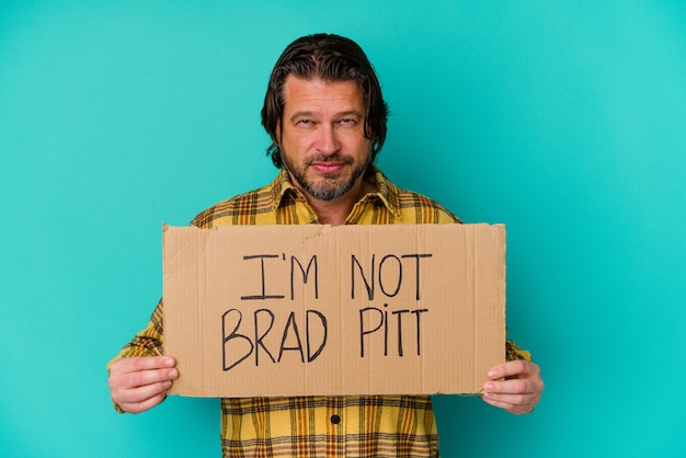 Hombre de mediana edad sosteniendo una pancarta que dice que no es una persona famosa