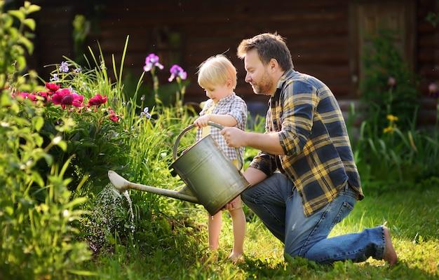 Hombre de mediana edad y su pequeño hijo regando flores en el jardín en un día soleado de verano