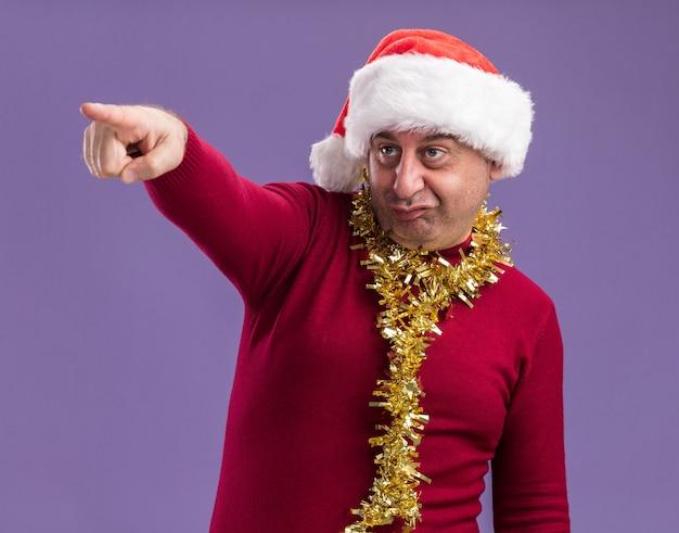 Hombre de mediana edad vestido con gorro de papá noel de navidad con oropel alrededor del cuello apuntando con el índice figner hacia el lado confundido y muy ansioso de pie sobre fondo púrpura