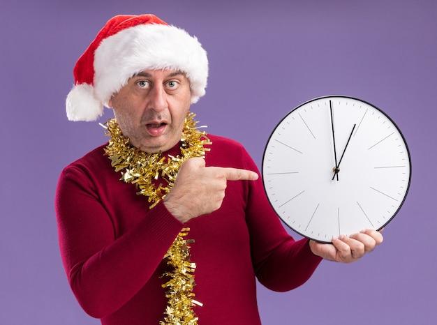 Hombre de mediana edad vestido con gorro de papá noel de navidad con oropel alrededor del cuello sosteniendo el reloj apuntando con el dedo índice mirando preocupado sobre fondo púrpura