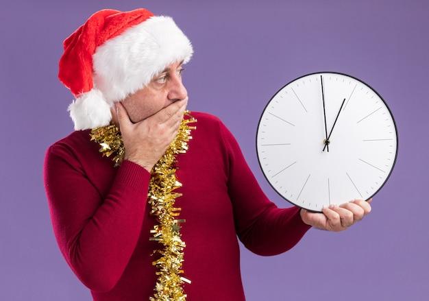 Hombre de mediana edad vestido con gorro de papá noel de navidad con oropel alrededor del cuello sosteniendo el reloj mirándolo preocupado cubriendo la boca con la mano de pie sobre fondo púrpura