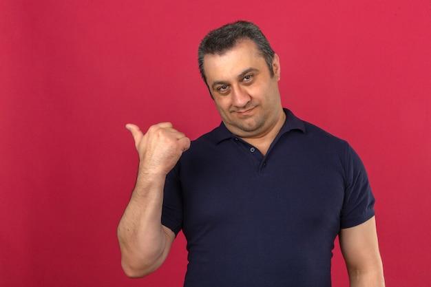 Hombre de mediana edad vistiendo camisa polo señalando algo detrás de él sobre la pared rosa aislado