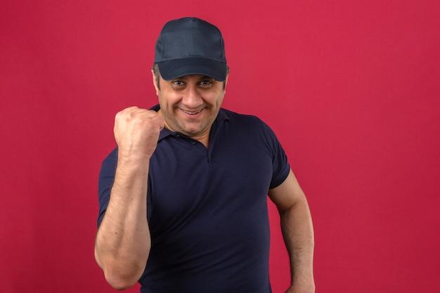 Hombre de mediana edad vistiendo polo y gorra mirando feliz levantando el puño como un ganador sobre pared rosa aislado